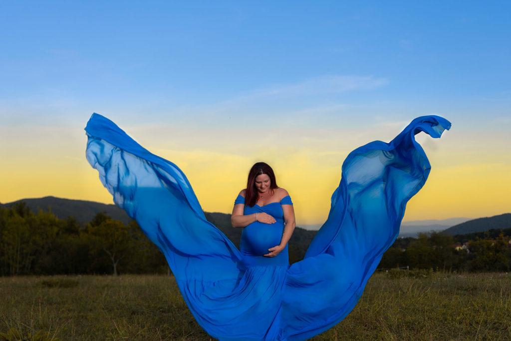 une femme encinte avec une robe qui forme un papillon avec un coucher du soleil grossesse creative dans la nature