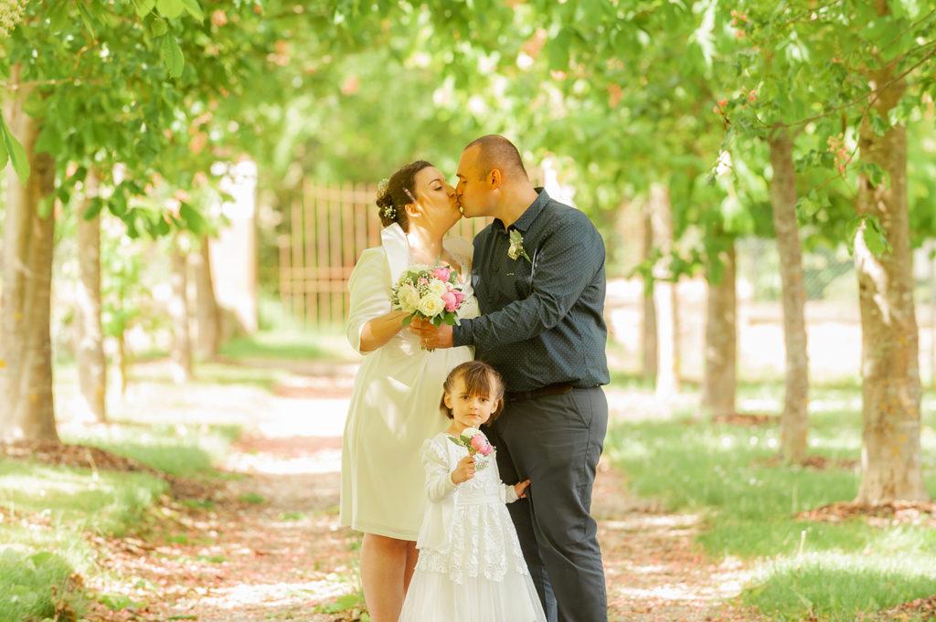 les maries s embrasse dans une allee d arbres avec leur petite fille un bouquet a la main