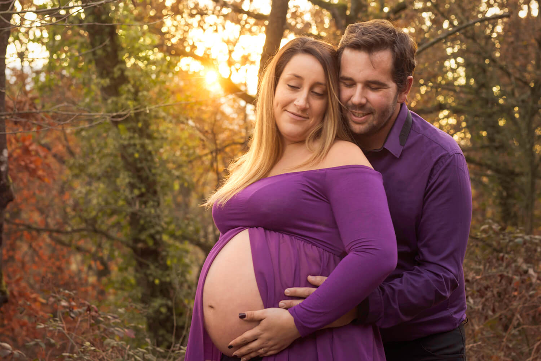 pendant un shooting photo de femme enceinte un couple s enlace dans un decor automnale avec un coucher du soleil