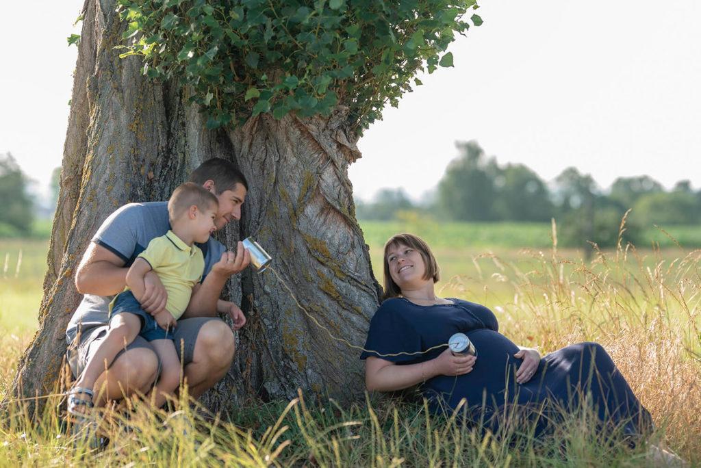 Seance grossesse une famille contre un arbre qui tiennent des converse en main en rigolant