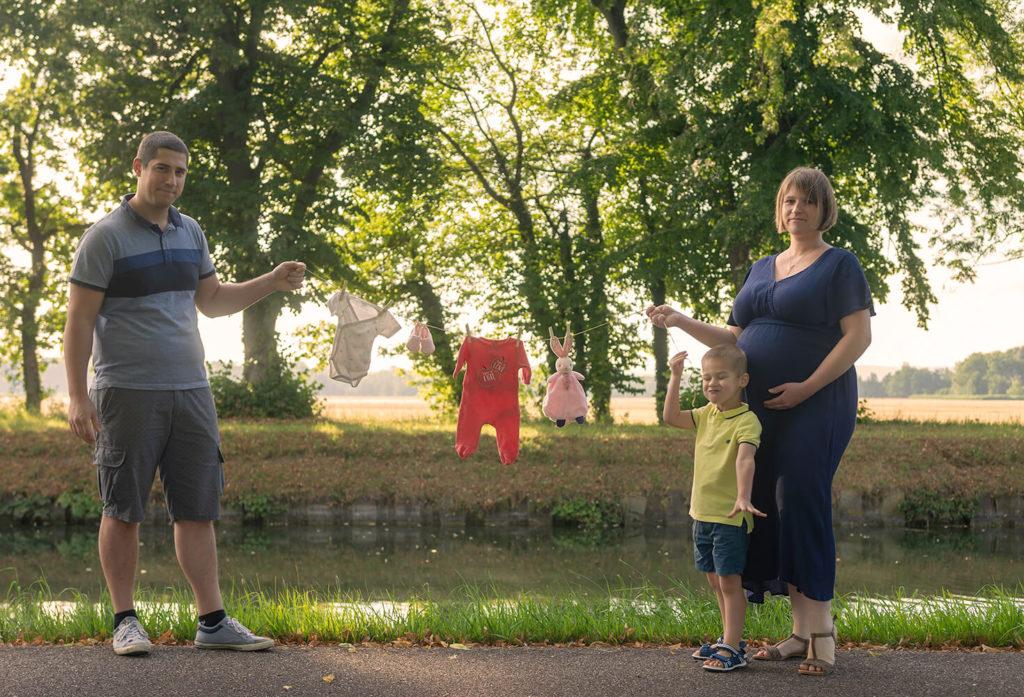 Seance grossesse les futurs parents tiennent une ficelle avec les tenues du futurs bébé