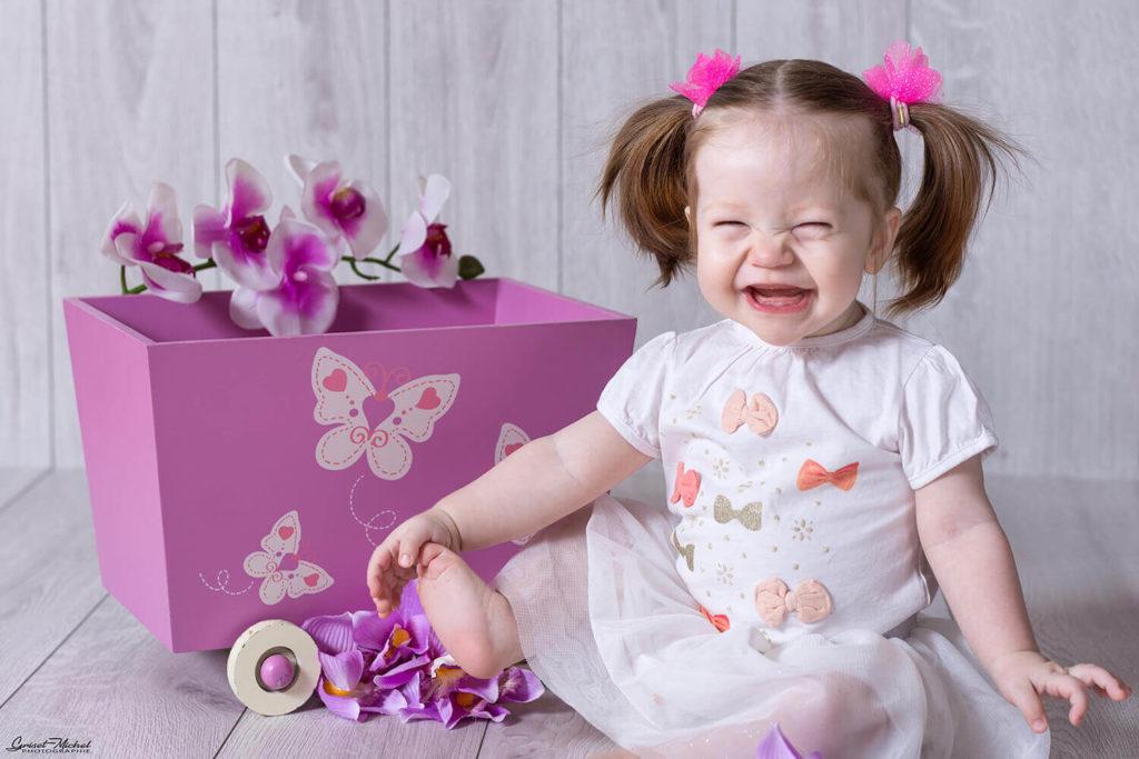 un bebe assis qui rigole avec un sourir enorme