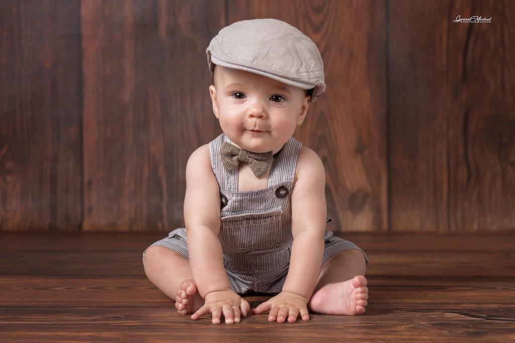 bebe assis avec un beret sur un fond en bois