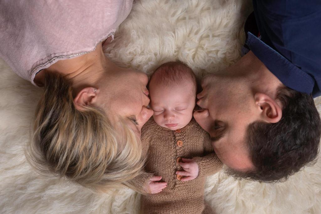 les parents allonge sur un tapis font un bisous en meme temps a leur petit garcon qui viens de naitre