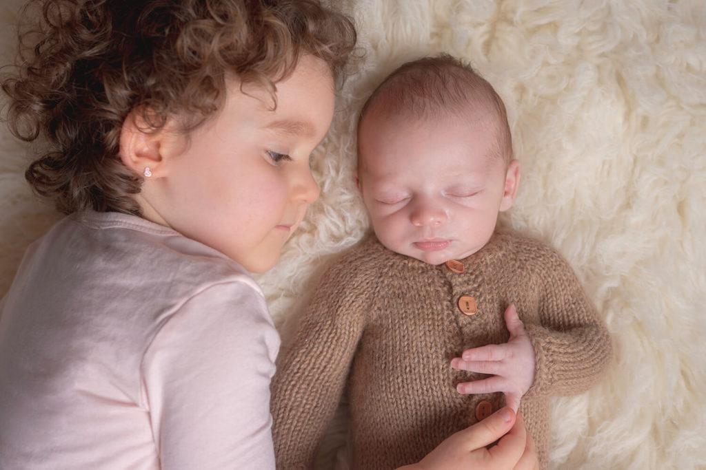 un bebe avec son aine son allonge sur un tapis beige moment de tendresse