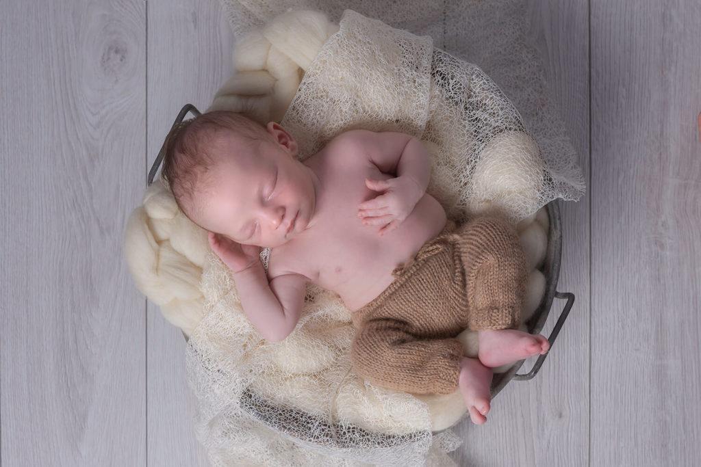 un bebe dans une bassine en metal sur un fond en bois avec un petit wrap