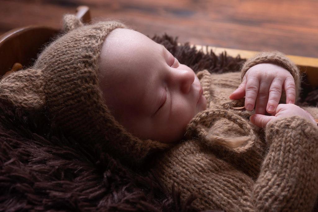petit garcon deguise en ours avec une tenue de laine dans un contenant pendant une seance photo