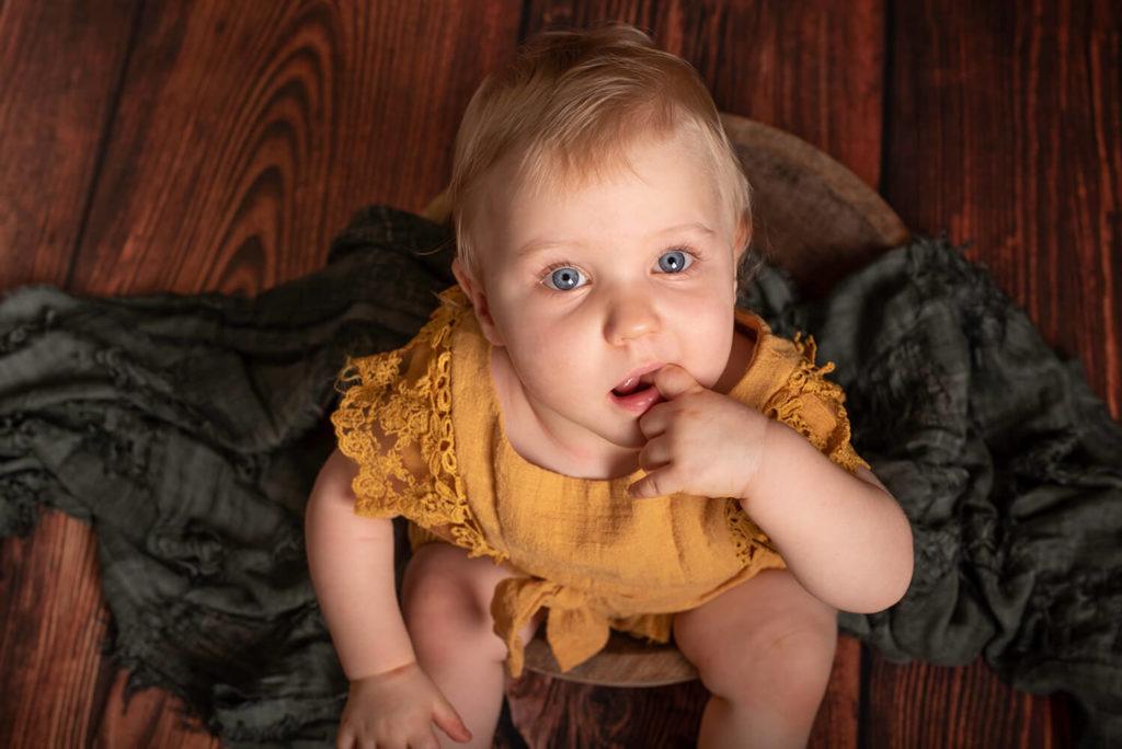 un bebe regard la camera vers le haut habille en costume vintage