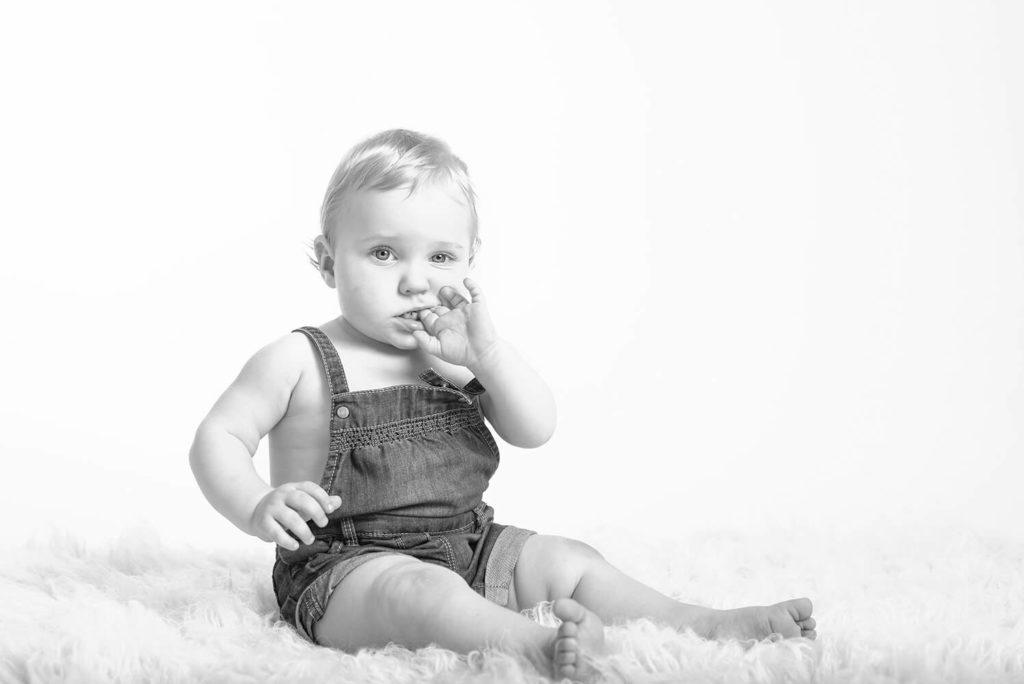 photo en noir et blanc d un bebe qui met les doigt dans sa bouche