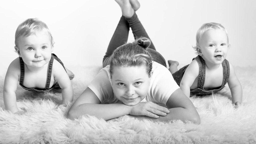 deux bebe assis a cote de leur grande soeur allonge photo en noir et blanc