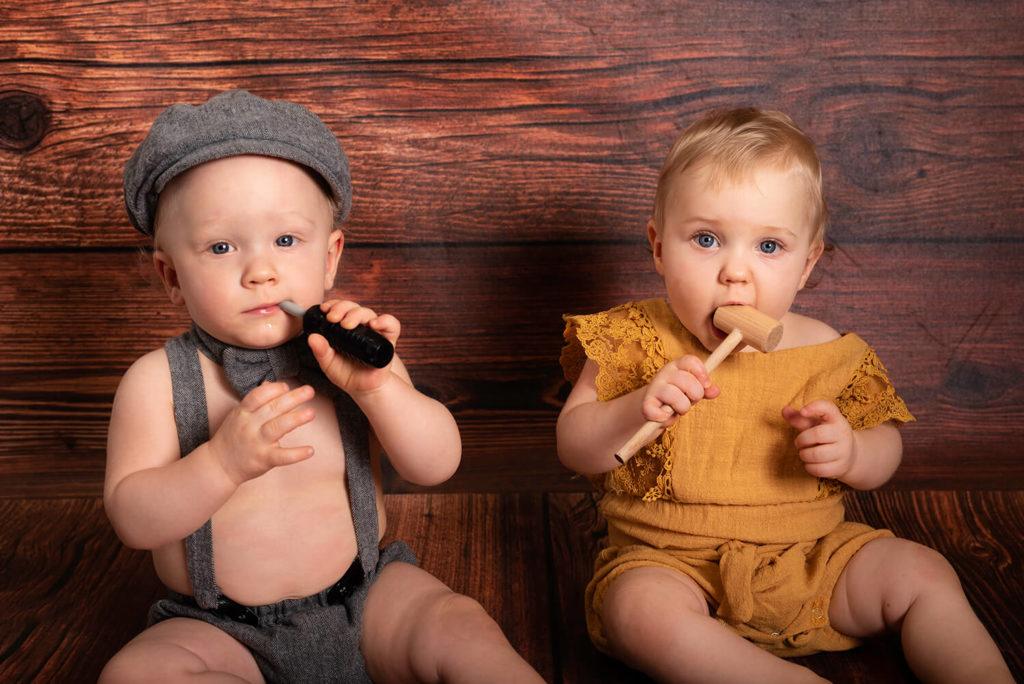 deux bebe habilles en vetements vintage sur un fond de studio de bois fonce