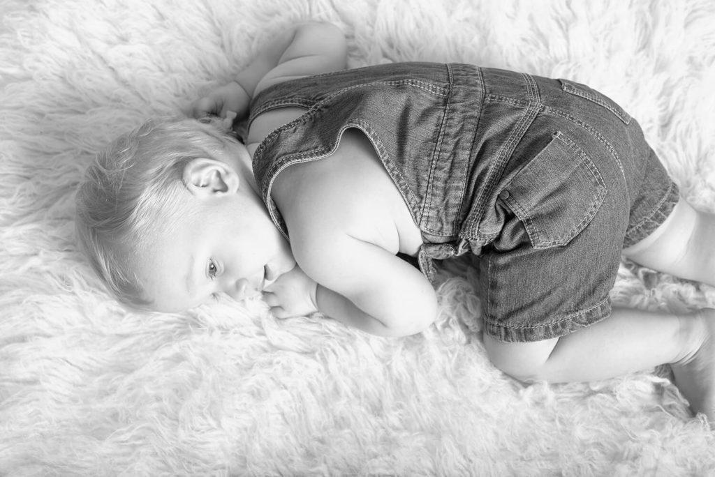 un nouveau ne allonge sur un tapis beige a poil long
