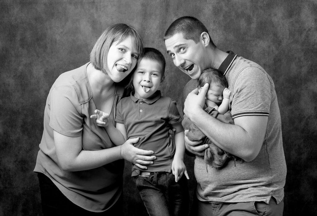 une famille avec un nouveau ne qui font des grimaces en studio photo
