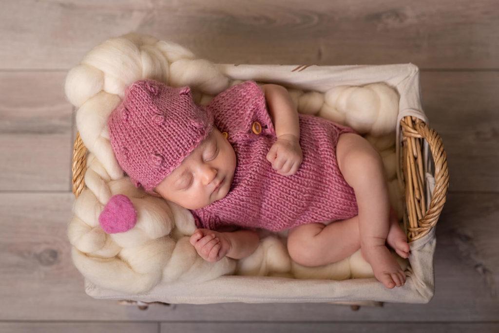 un nouveau ne avec une tenue rose en laine un petit coeur rose dans un contenant en bois