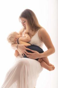 une famille en studio avec un bebe qui prend le sein de sa mere pour allaiter
