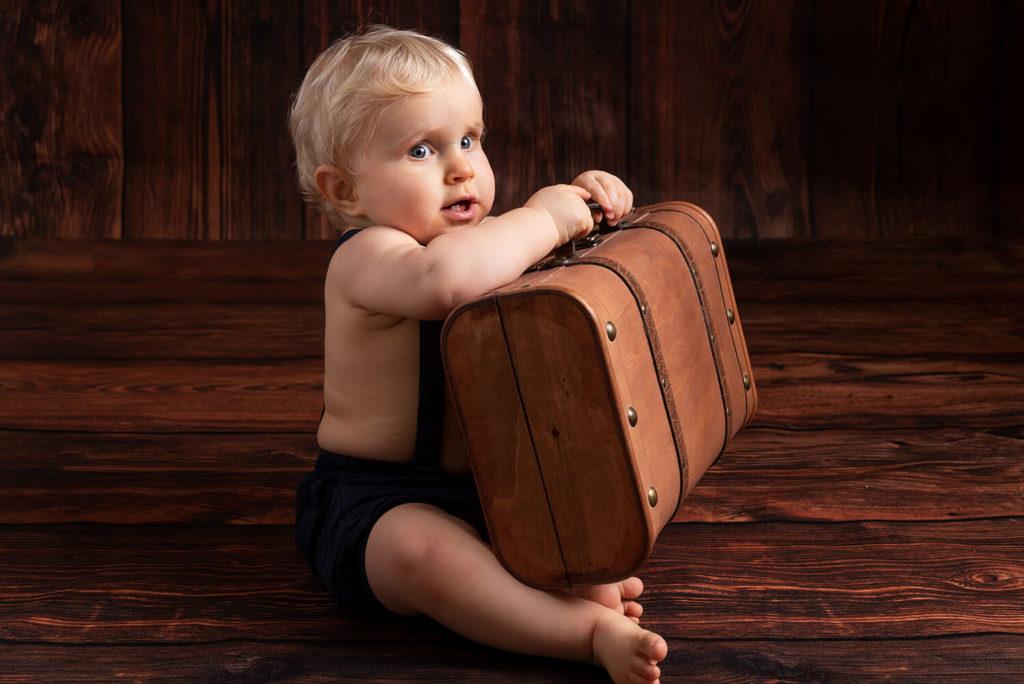 un bebe tiens en main une valise vintage en faisant une tete rigolote