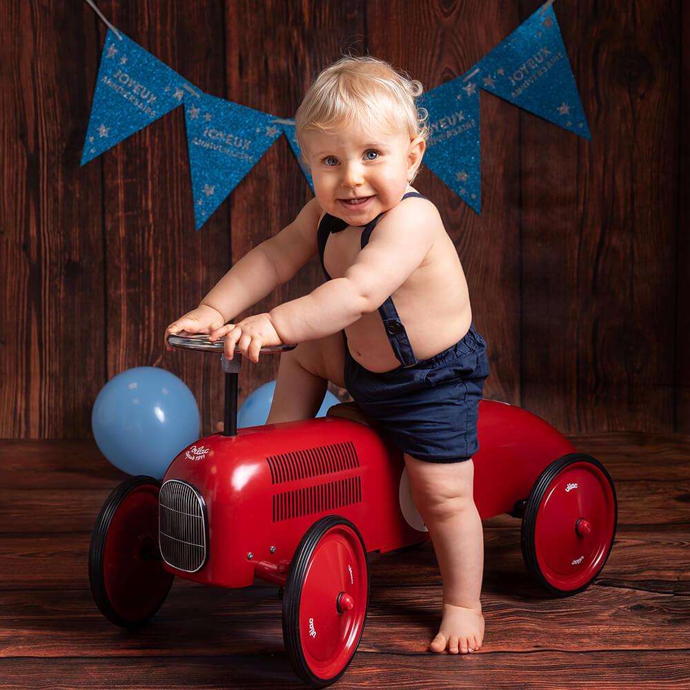 pour ses 1 an ce petit garcon pose en studio photo sur selestat sur une voiture bagherra vintage