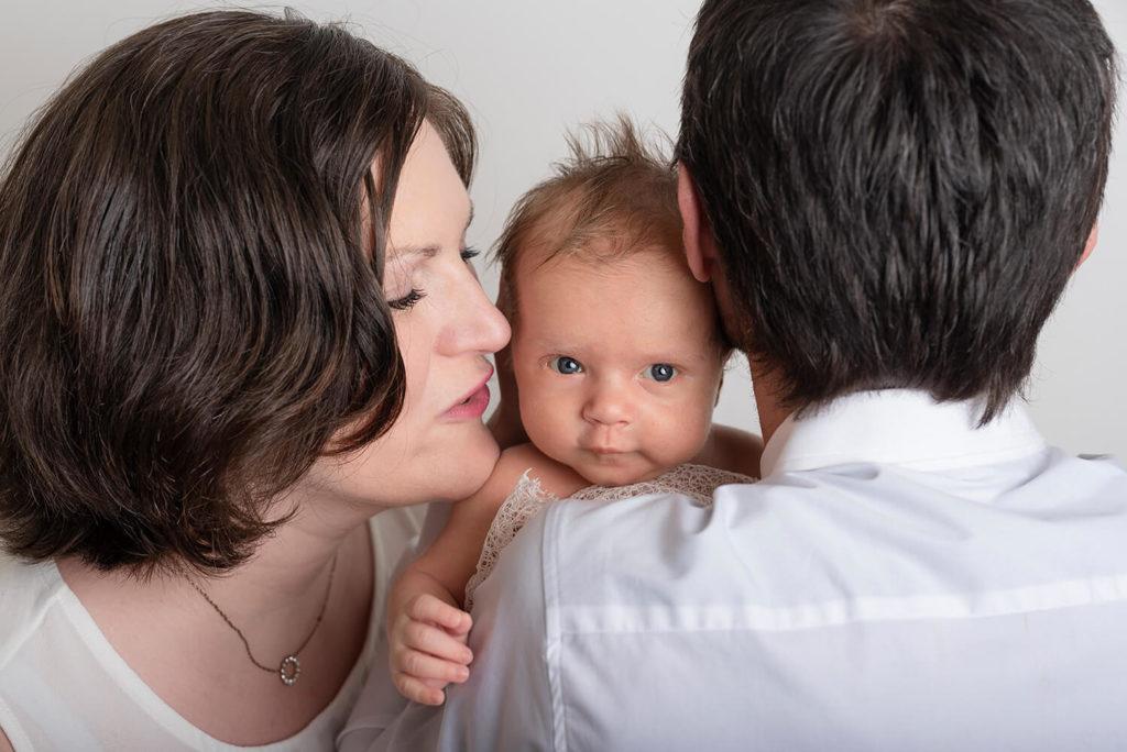 un nouveau ne dans les bras de ses deux parents qui regard le photographe en souriant