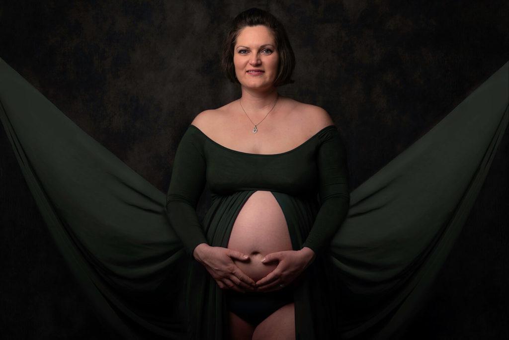 une maman regard le photographe avec une robe kaki en forme de papillon